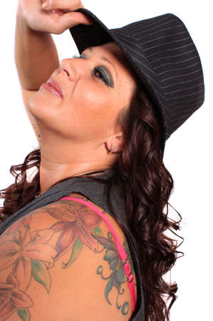 arm: Pretty tattooed woman in her mid thirties smiling holding a fedora to her head Stock Photo
