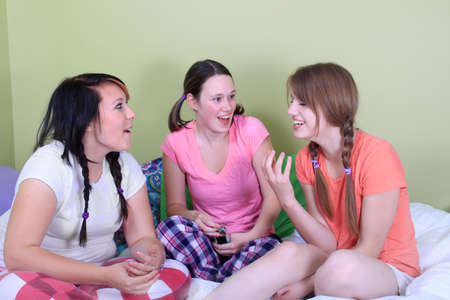 Group of three teenage girls hanging out on a bed in their pajamas ready for a sleepover or slumber party and telling stories or gossiping photo