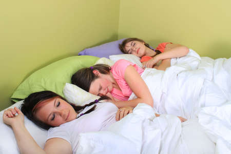 Three pretty teenage girls sleeping on a bed at a sleepover or a slumber party photo