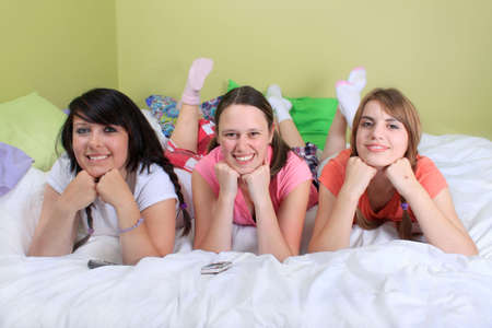 slumber: Group of three teenage girls hanging out on a bed in their pajamas ready for a sleepover or slumber party Stock Photo