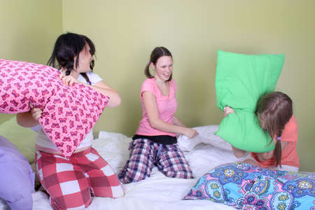 Three teenage girls in their pajamas with pigtails or braids having a pillow fight on a bed at a sleepover Stock Photo - 7937077