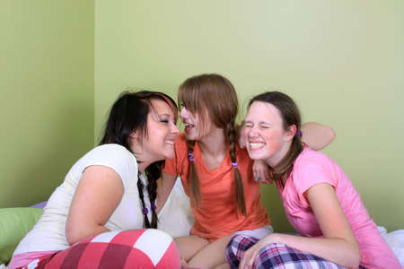 Three teenage girls have a slumber party or sleepover and one is whispering secrets in the others ear