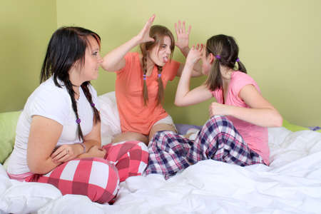 Teen girls in their pajamas having a sleepover making funny faces at eachother while sitting on the bed photo