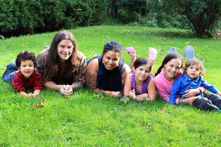 Mixed race beautiful ethnic family with parents and four children laying on the grass photo