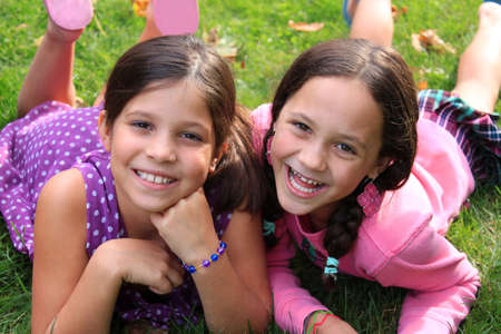 pretty young girl: Two young girls in the ages of ten and eight that could be sisters or best friends laying on the grass and smiling whitle wearing colorful clothing