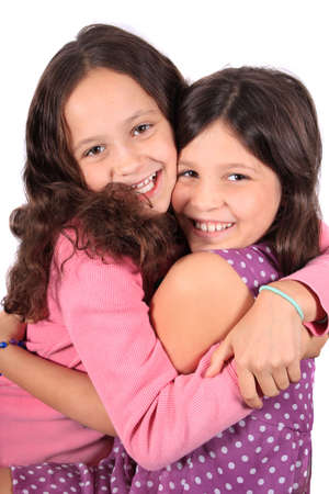 Pretty young girls in the ages of eight and ten who could be sisters or best friends dressed in colorful clothing and hugging photo