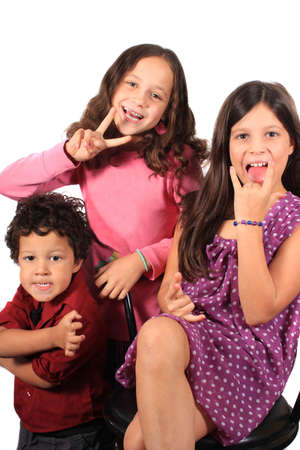 Cute kids playing making funny faces and gestures, two adolescent girls one little toddler boy photo