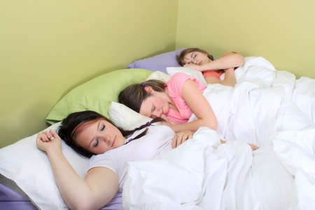 Three pretty teenage girls sleeping on a bed at a sleepover or a slumber party Stock Photo - 7937233