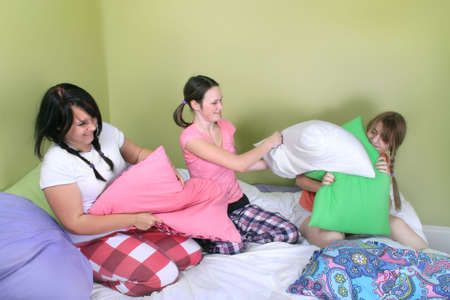 pillow fight: Three teenage girls in their pajamas with pigtails or braids having a pillow fight on a bed at a sleepover