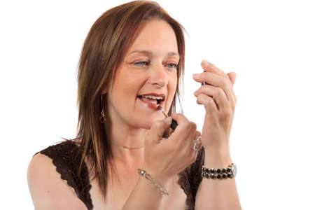 lipgloss: Woman holding hand mirror applies lipgloss to lips