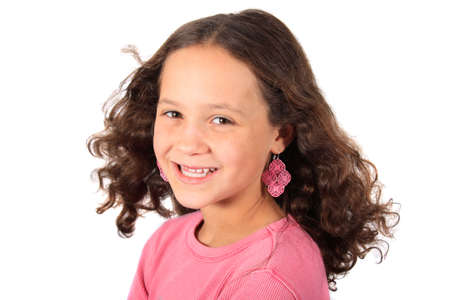 Pretty young ten year old girl with a big smile dressed in pink on a white background