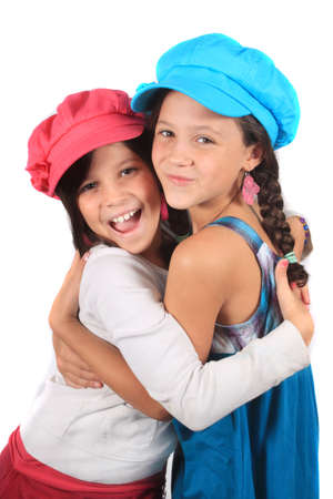 Pretty young girls in the ages of eight and ten who could be sisters or best friends hugging dressed in colorful clothing and hats Stock Photo
