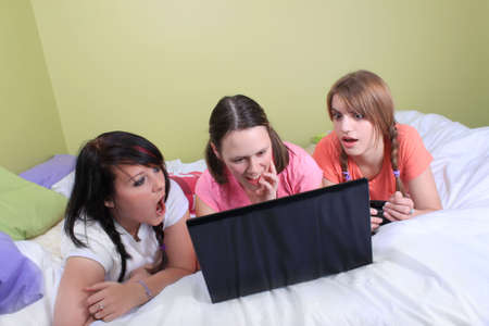 reacting: Group of three teenage girls with pigtails and braided hair having a slumber party or sleepover laying on a bed reacting to screen on laptop
