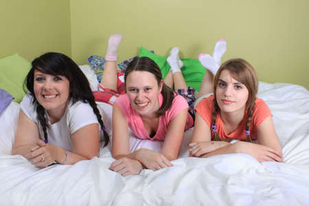sleepover: Group of three teenage girls hanging out on a bed in their pajamas ready for a sleepover or slumber party Stock Photo