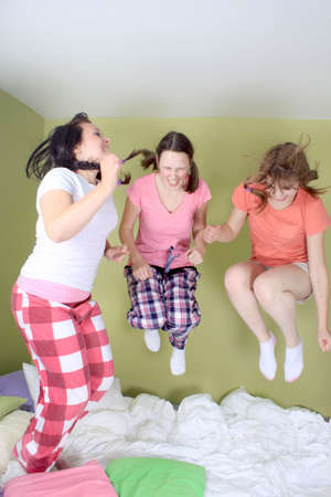 slumber: Teen girls having a sleepover jumping up and down on the bed (some motion blur)