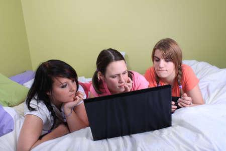 soir�e pyjama: Groupe de trois adolescentes avec des nattes et tresses avoir une soir�e pyjama ou soir�e pyjama pose sur un lit � l'aide d'un ordinateur portable et les t�l�phones portables
