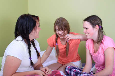 soir�e pyjama: Groupe de trois adolescentes fl�ner sur un lit dans leurs pyjamas pr�ts pour une nuit�e ou parti de sommeil  Banque d'images