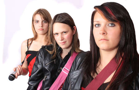 Three teenage girls in a music band holding instruments on a white background (focus on girl in the middle) photo