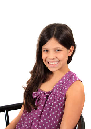 Pretty eight year old adolescent multi ethnic girl with long dark hair, sitting on a stool with white background