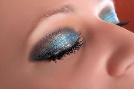 metallic: Closeup of eye makeup on lid in metallic blue in peacock colors with shallow depth of field