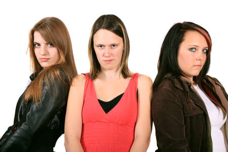 Three pretty teenaged girlfriends hanging out on a white background looking serious with attitude photo