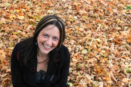 sitting on the ground: Beautiful woman in her forties is happily sitting on the ground covered by a bed of autumn leaves