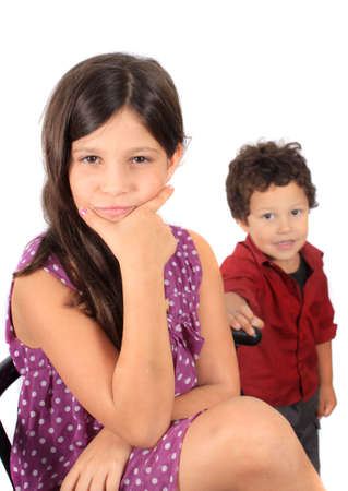 A multiracial girl with hand on her chin looking pensive and a toddler  boy in the background photo