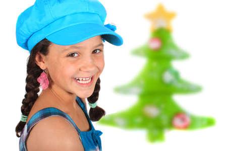 Pretty ten year old adolescent multi ethnic girl with braids and christmas tree in the  background wearing a colorful blue hat and big toothy smile