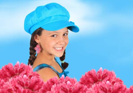 Pretty girl with funky blue hat standing behind pink flowers  and in front of a bright blue spring sky