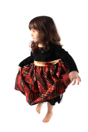 velvet dress: Cute little three year old girl in a fancy plaid and velvet dress dancing on a white background