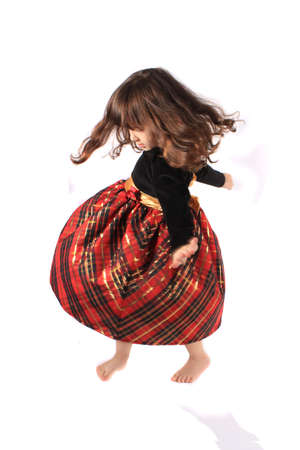 velvet dress: Cute little three year old girl in a fancy plaid and velvet dress dancing and twirling on a white background with selective focus and motion blur Stock Photo