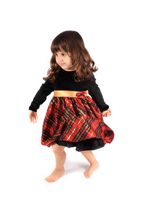 velvet dress: Cute little three year old girl in a fancy plaid and velvet dress dancing and twirling on a white background