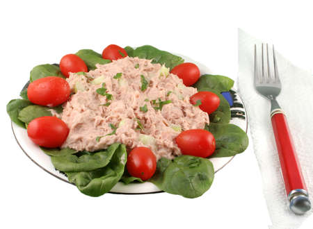Healthy meal of tuna fish salad with cherry tomatoes and spinach on a white background