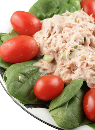 Healthy meal of tuna fish salad with cherry tomatoes and spinach on a white background with shallow depth of field Stock Photo