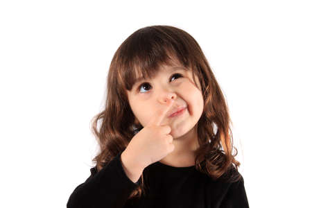 3 year old: Little three year old brunette little girl holding her finger close to her nose with a thinking expression, hmm