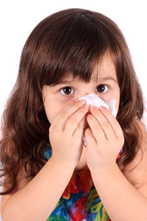 allergies: Little three year old girl having the sniffles and wiping her nose with tissue from being sick or allergies