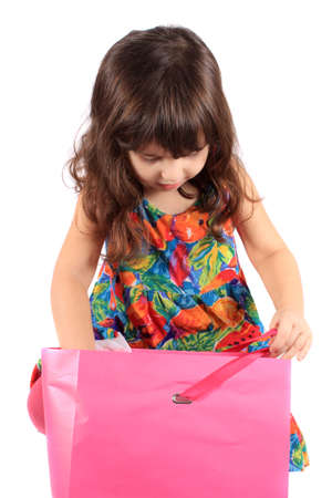 anticipating: Cute little three year old girl looking to see whats in the  pink shopping back on a white background Stock Photo
