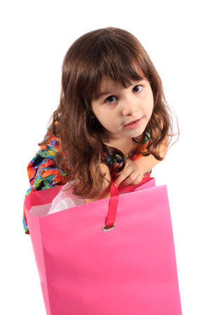 Cute little three year old girl looking to see what's in the  pink shopping back on a white background Stock Photo - 8244696