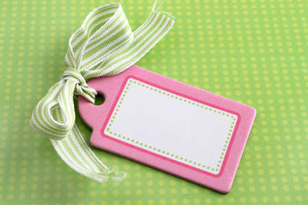 Pretty blank pink gift tag with ribbon on green polkadot background Stock Photo - 8244708