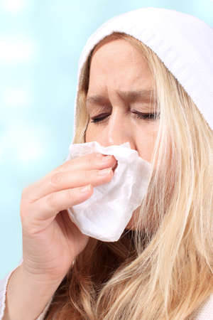 sniffles: Woman wearing a hooded sweater holds a tissue due to sniffles or sneezing because of a cold or allergies