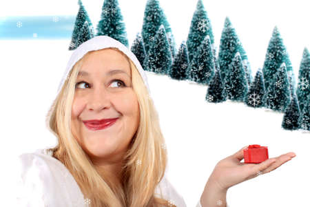 Happy smiling blonde woman showing a small red present box in her hand with a snowy hill background photo
