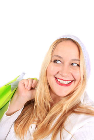 Pretty woman with a big smile holding a green shopping gift bag on a white background photo