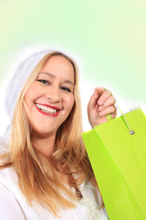 Pretty woman with a big smile holding a shopping gift bag on a white background photo