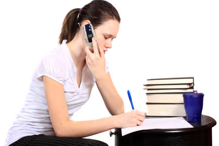 phone: Young teenaged girl talking on the phone and writing on a paper with textbooks, doing her homework
