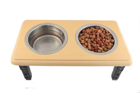 morsels: Dog  bowls full of food bits and water on a wooden table on a white background Stock Photo