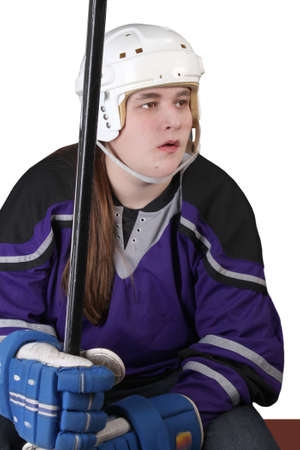player bench: Teen male hockey player with helmet, gloves, and stick sitting on a bench isolated on a white background