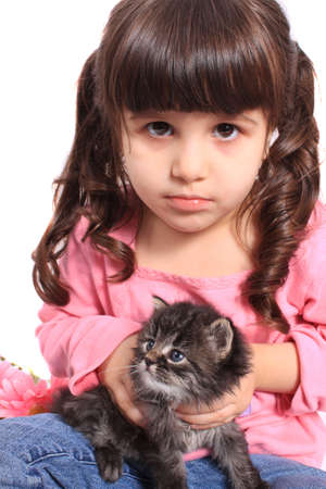 Cute little four year old girl in pigtails holding a little kitten on a white background