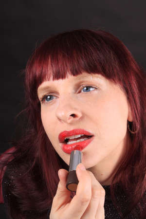 luscious: Close-up of woman applying red lipstick to her luscious lips