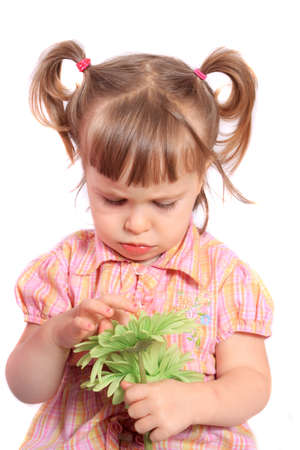 two year old: Grumpy looking two year old girl holding a green flower