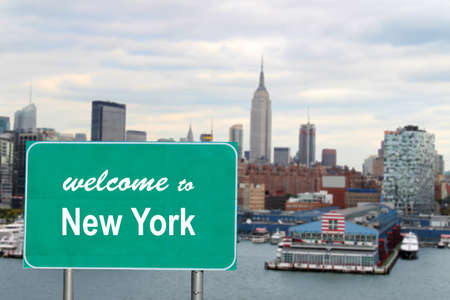 Welcome to New York sign with famous skyline and boat docks along the Hudson River